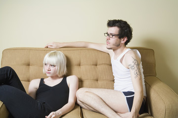A young couple sitting on a sofa