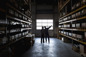 Two manual workers in a metal parts warehouse