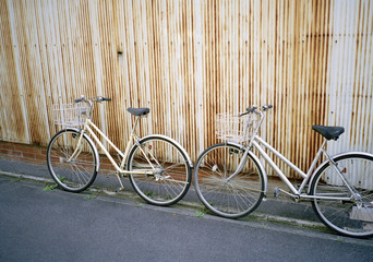 Two bicycles leaning on a wall
