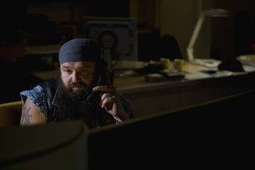 A biker sitting in a darkened office on the phone