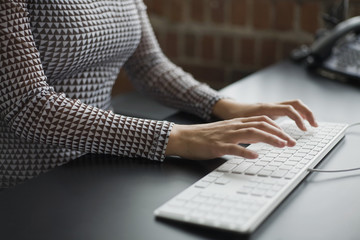 A woman typing on a keyboard