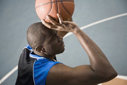 A man preparing to shoot a basketball on court