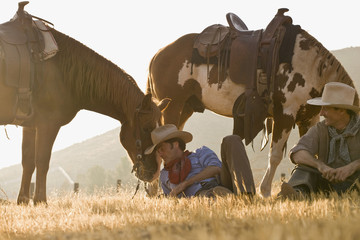 Two cowboys resting with their horses