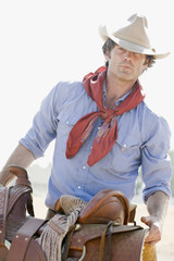 A cowboy carrying a horse saddle