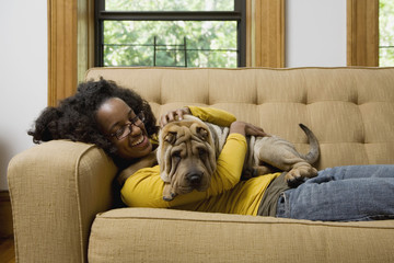 A woman lying a couch with her Shar-Pei