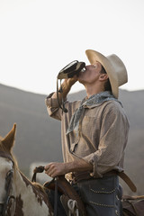 A cowboy sitting on a horse and drinking from a hip flask