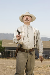 Portrait of a cowboy aiming his gun