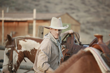 A cowboy working on a ranch with horses