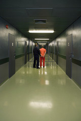 Rear view of prisoner and guard standing in corridor