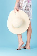 Cropped image of a girl holding beach hat over blue