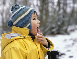 A young boy licking a snowball