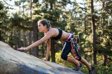 Sporty woman climbing a rock