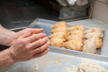 Hand of a cook holding an open typical rice arancino with chicken before modelling it in a cone shape