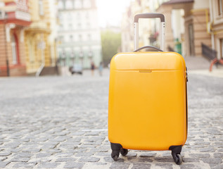 Fototapeta Orange suitcase on the road in city. Summer vacation and travel concept obraz