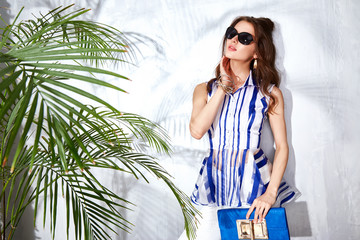 Sexy beautiful woman luxury chic fashion gold sunglasses brand hand bag trendy jewelry style for party date glamour pose summer palm clothes collection brunette hair accessory model