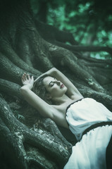 beautiful young woman in a long white dress with long wavy hair, lying on the large roots of a tree with eyes closed. Fairy tale. Dream