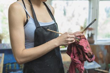 Midsection of woman cleaning paintbrush with fabric in studio