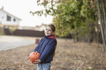 Portrait of cute girl holding pumpkin outdoors