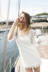 девушка стоит на палубе яхты и держится за трос