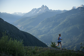 Woman jogging on path in mountain range