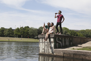 Multi-ethnic friends enjoying on retaining wall by canal