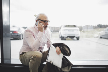 Man talking on phone while sitting by glass window at car showroom