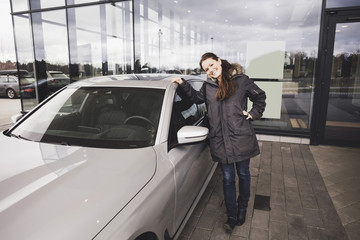 Portrait of smiling woman standing by car against showroom