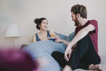 Happy young woman holding birthday cupcake with candle while looking at man on bed