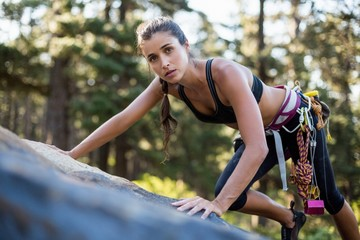 Woman rock climbing and looking the camera on the wood