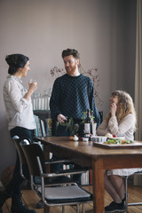 Young man with female friends having breakfast at home