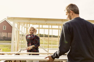 Man assisting woman in making shed at farm