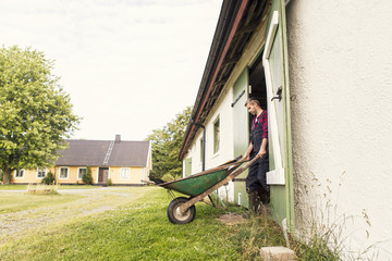 Man with wheelbarrow walking out of barn at farm
