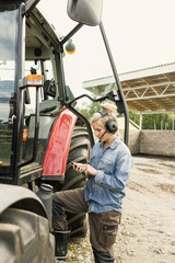Side view of woman using phone while standing by tractor at farm