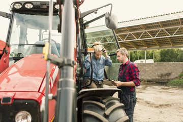 Couple discussing over document by tractor at farm