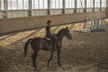 Side view of woman riding horse in training stable