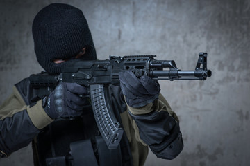 Terrorist in balaclava with automatic rifle in hands