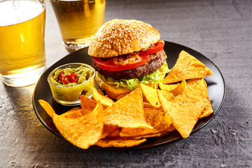 Hamburger, tortilla chips and two glasses of beer