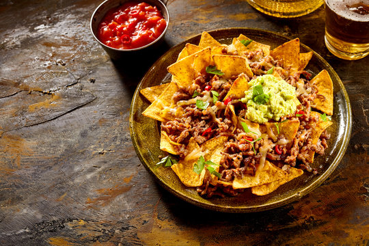 Chips with cheese, meat, guacamole and salsa