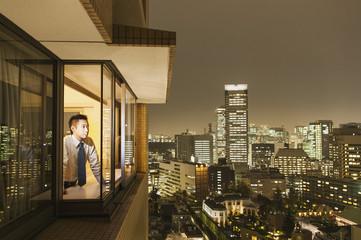 Businessman looking at illuminated cityscape through window at dusk