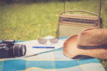 Kamera, Sonnenbrille und Hut auf Picknickdecke, altes Radio im Hintergrund