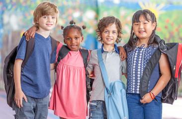 Happy multi ethnic classmates embracing in schoolyard, happiness
