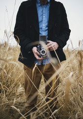 Low section of man taking picture with vintage camera in field