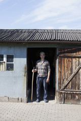 Portrait of confident mature man standing at the entrance of poultry farm