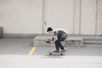 Full length side view of man video shooting while skateboarding outdoors