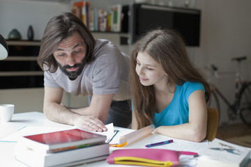 Father assisting daughter in doing homework at table