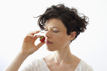 A woman smelling strawberry over white background