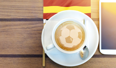Football fan latte art, next to smart phone and flag of Spain. Sport apps