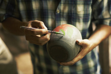 Midsection of male potter painting pot in workshop