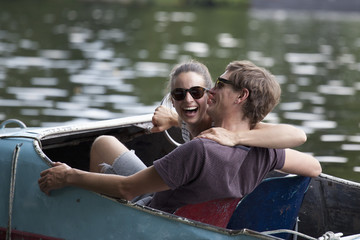 Young couple riding paddle boat, laughing