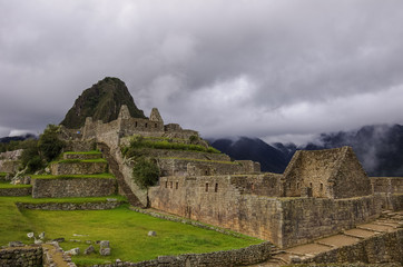 View of temple ruins and terrace in Lost Inca City of Machu Picchu. Low clouds and mountains at background. Cusco Region,Sacred Valley, Peru